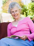 Senior woman reading book outside