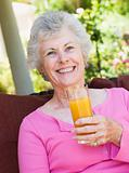 Senior woman enjoying glass of juice
