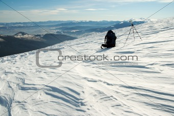 knapsack and tripod in winter mountains