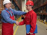 two workers handshake in warehouse