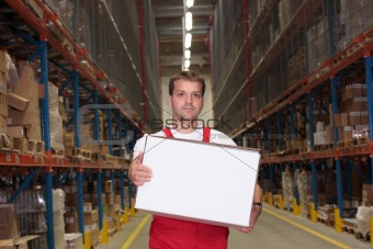 worker in uniform carrying box in warehouse