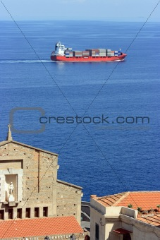 Cantainer cargo ship over Scilla cathedral