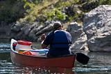 man paddling his canoe on river