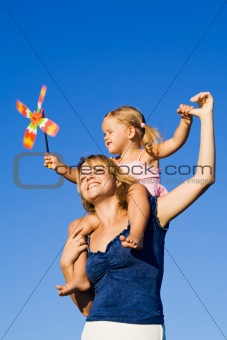 Little girl and woman with a pinwheel toy outdoors