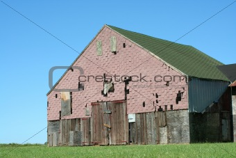 Old barn with grass and blue sky