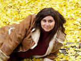 young plus-size model with yellow fall leaves and jacket