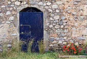 Blue metallic door on stone building