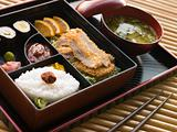 Tonkatsu Box and Miso Soup with Pickles and Sushi on a tray