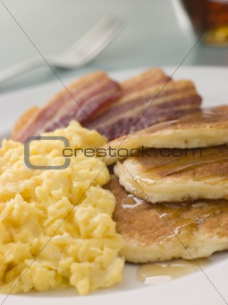 American Pancakes with Crispy Bacon and Scrambled Eggs and Maple