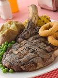 Ribeye Steak on the bone with Baked Potato Peas Onion Rings and
