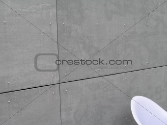 grey concrete wall and white chair