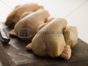 Three Whole Poussins on a Chopping Board