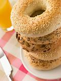 Stack of Seeded Bagels with a Glass of Orange Juice
