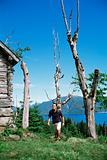 Man hiking up to a wooden cabin