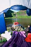 Woman washing face in lake,  view through tent entrance