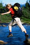 Hiker jumping from rock to rock while crossing river