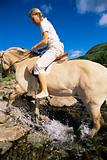 Young woman crossing a river by horse