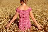 Rear view of young woman standing in wheatfield