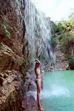 Woman in bikini standing under waterfall