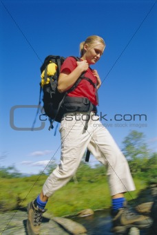 Young woman wearing backpack stepping across river