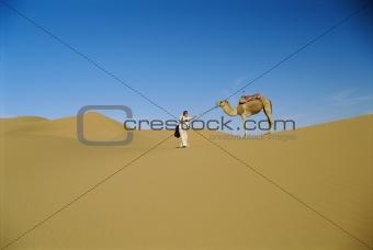 Man in desert with stubborn camel