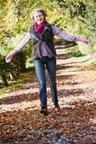 Senior woman enjoying walk through woods