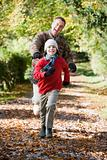 Grandfather and grandson running through woods