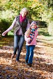 Grandmother and granddaughter playing in woods