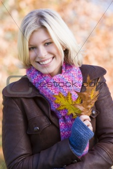 Young woman on walk holding leaf