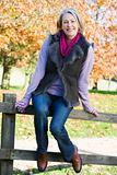 Senior woman sitting on fence