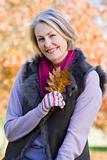 Senior woman holding autumn leaf outdoors