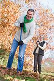 Senior couple tidying autumn leaves