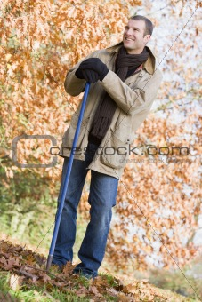 Man tidying leaves in garden