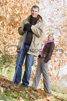 Couple clearing autumn leaves