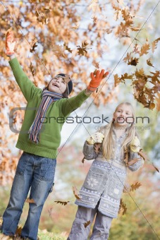 Two children throwing leaves in the air