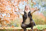 Senior woman throwing leaves in the air