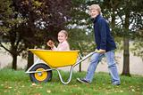Boy pushing girl in wheelbarrow