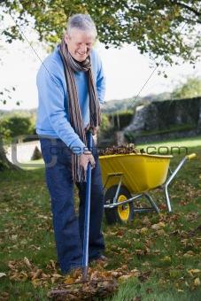 Senior man collecting leaves in garden