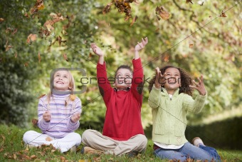 Group of children playing in autumn leaves