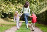 Mother and children walking on woodland path