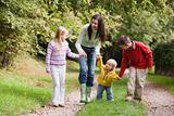 Mother and children walking along woodland path