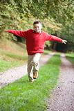 Young boy running along woodland path