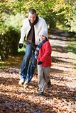 Father and son running along woodland path