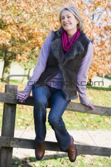 Senior woman sitting on fence