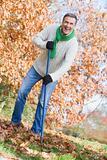 Senior man tidying leaves in garden