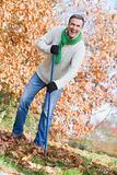 Senior man tidying leaves in garden