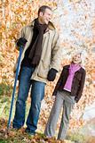 Couple raking up autumn leaves