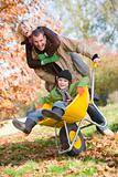 Father and mother pushing son in wheelbarrow