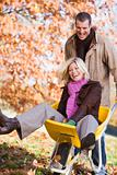 Man pushing woman in wheelbarrow