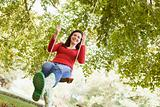 Young woman on tree swing